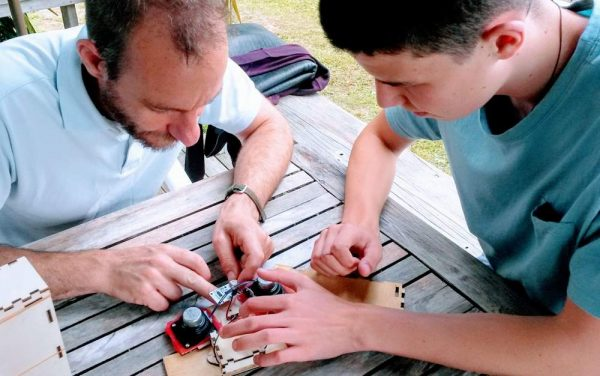 Man and teenage boy working on Bluetooth speakers